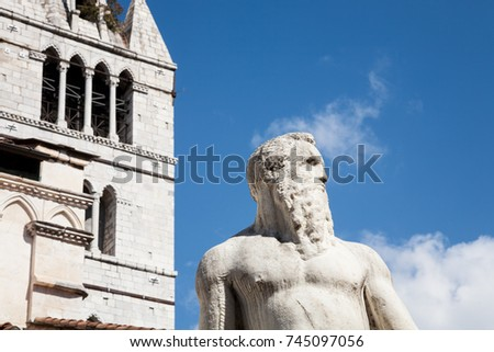 The historic 16th century marble statue of the Giant with the cathedral tower in the background in Carrara in Tuscany, Italy