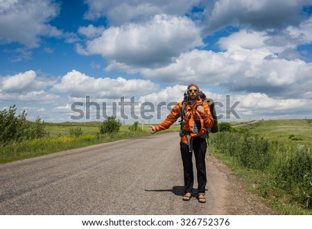 The Hitchhiker. Man Hitchhiking on a Country Road in Rural Nevada Desert. Men Catching Some Car. - stock photo