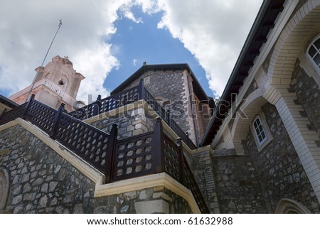 The Holy Monastery of the Virgin of Kykkos in Troodos mountains, Cyprus. Fragment of the main courtyard, belfry and arcade. - stock photo