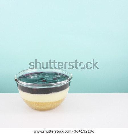 The homemade blueberry cheese cake in the small glass bowl on white table.