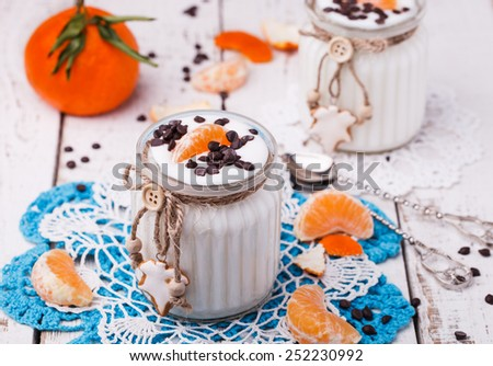The homemade yogurt in a jar with tangerines and chocolate - stock photo
