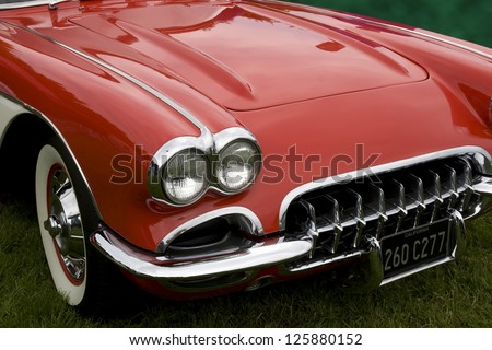 the hood of a classic sports car with an altered number plate - stock photo