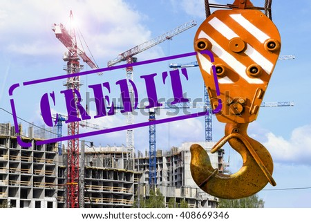 "The hook of the crane and the stamp ""credit"" against the construction - stock photo"