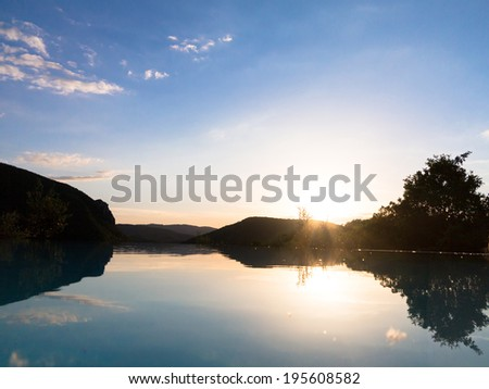 The horizon and reflections in an infinity swimming pool against a dusk sky - stock photo