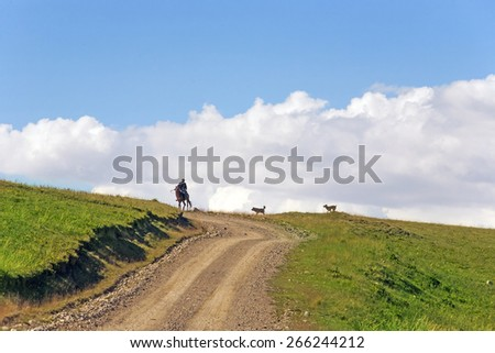 The horseman in the mountains on the background of clouds - stock photo