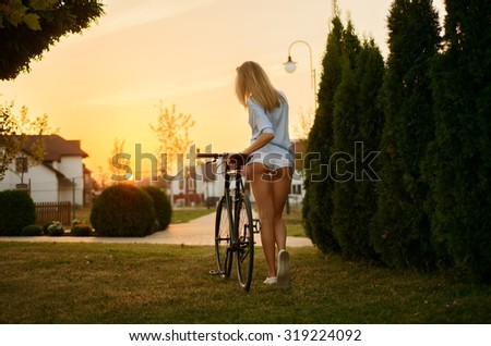 The hottest ass in shorts of blond girl going with her bike in sunset - stock photo