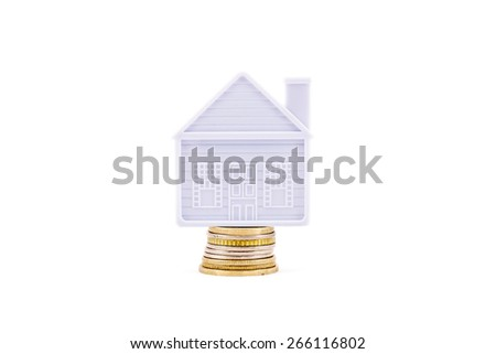The house stands on a few coins on a white background - stock photo