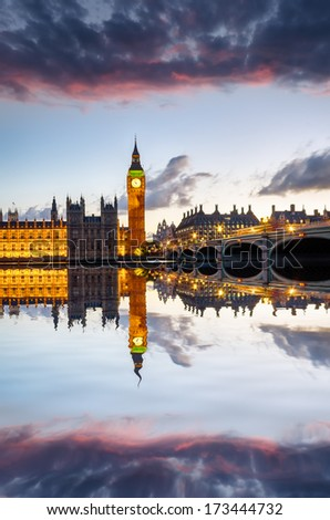 The Houses of Parliament, Big Ben and Westminster Bridge under a fiery sunset sky - stock photo