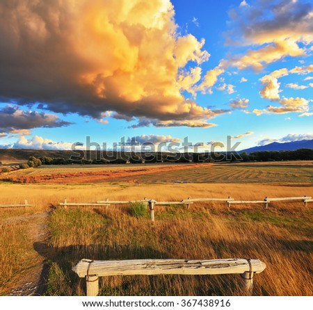The huge cloud lit yellow-orange rays of sunset. Cozy wooden bench by the side of the road in Argentina - stock photo