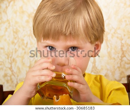 The hungry little boy drinks a glass with juice
