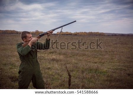 The hunter shoots from weapon at ducks