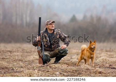 the hunter with a gun and a dog - stock photo