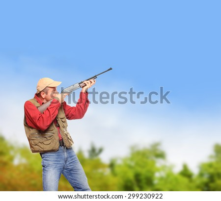 The hunter with hunting rifle aiming at blue sky. Picture with space for your text. - stock photo