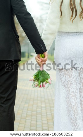 The husband and the bride holding a bouquet, on nature