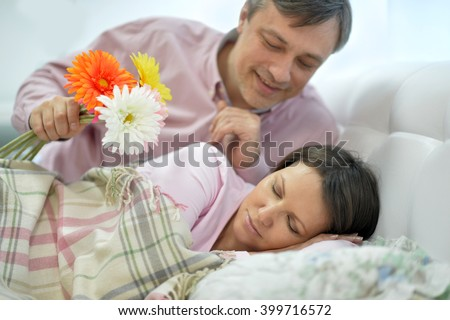 the husband gives his wife flowers in bed - stock photo