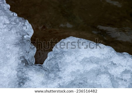 The ice edge is covered with snow on the background of the current water - stock photo