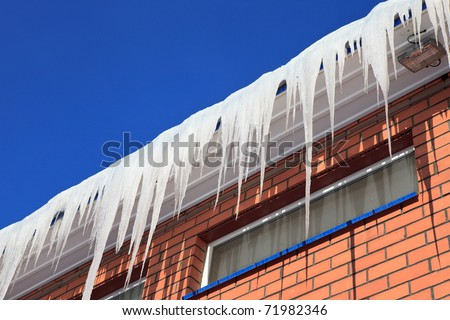 The ice on the roof of the brick house