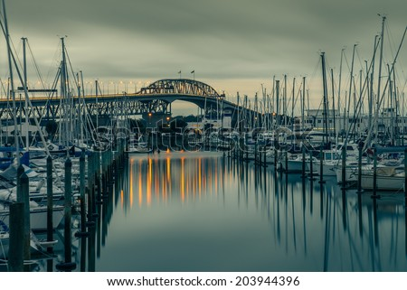 The iconic Auckland Harbour Bridge reflecting on Westhaven Marina - stock photo