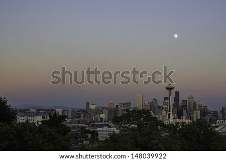 The iconic view of the Seattle skyline at sunset from Kerry Park with full moon overhead. - stock photo