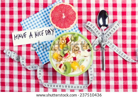 The idea of healthy diet, dietary breakfast. Wishing a nice day. Losing weight with the help of a fruit diet. Fruit salad with yogurt and half a grapefruit for breakfast. Spoon with measuring tape. - stock photo