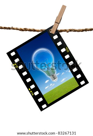 The image blub lamp and grass meadow and blue sky in color transparency films hang on the rope cliped with wooden clip path - stock photo