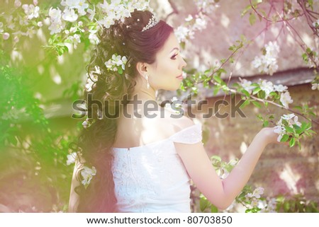The image of a beautiful bride in a blossoming garden - stock photo