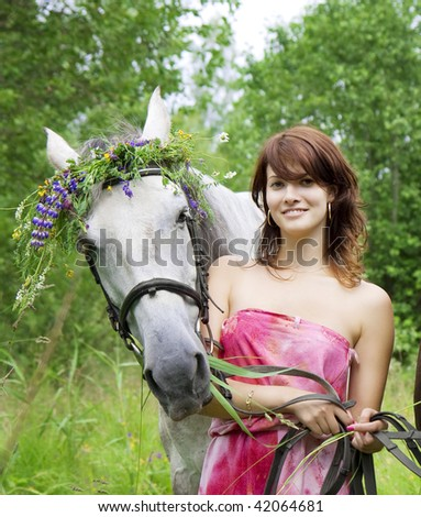 The image of a beautiful brunette girl with horses - stock photo