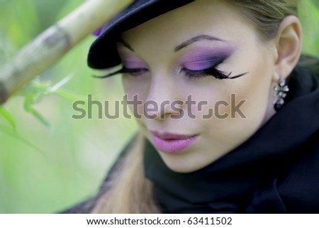 The image of a beautiful girl in a purple dress in the autumn park