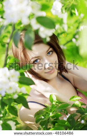 The image of a beautiful girl on a background of flowering trees - stock photo