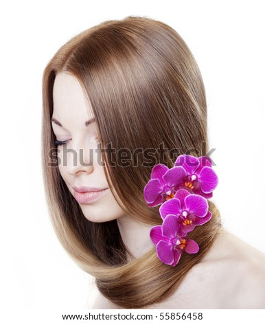 The image of a beautiful girl with with orchids in her gorgeous hair - stock photo