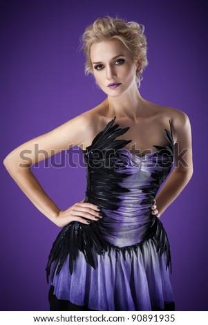 The image of a beautiful luxurious woman on purple background. Studio shot - stock photo