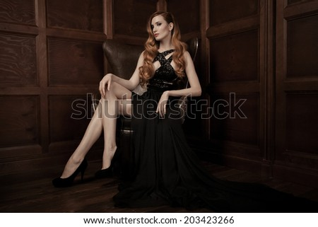 The image of a beautiful luxurious woman sitting on a leather vintage chair. - stock photo