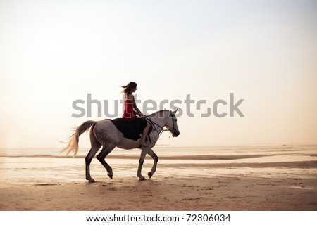 The image of a girl riding a horse on the background of the sea - stock photo
