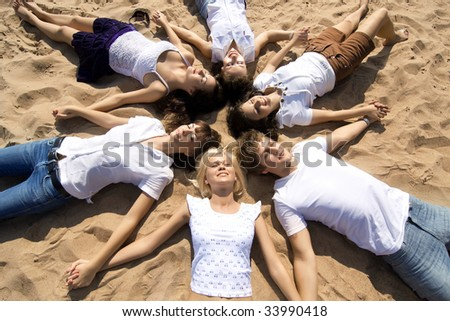 The image of a group of friends, lying on the sand their heads together - stock photo