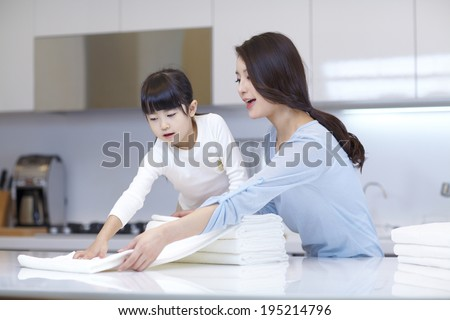 the image of a happy Asian family folding beach towels - stock photo