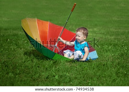 The image of a little boy with a big rainbow umbrella