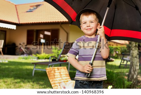 The image of a little boy with a big umbrella