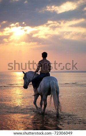 The image of a male riding a horse on the background of the sea - stock photo