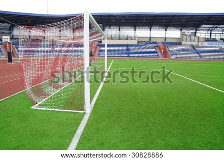The image of a stadium and a goal under the foreground. There is white background instead of the sky