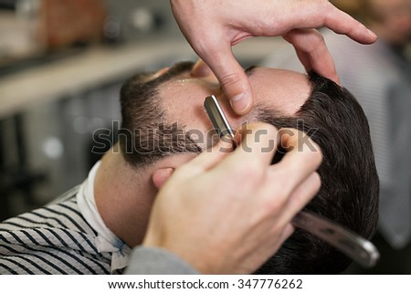 The image of a straight razor shaving his beard. Client with beard and mustache while shaving in the men's barber shop.
