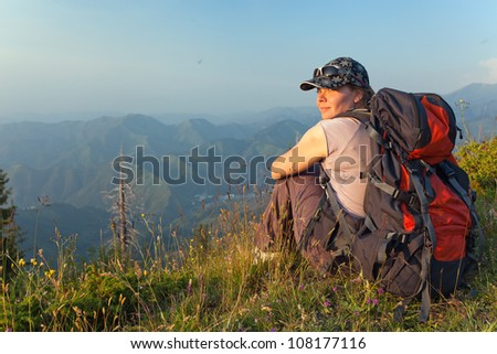 The image of a young woman sitting at the top of the mountain and looking at camera at sunset, Kazakhstan. - stock photo