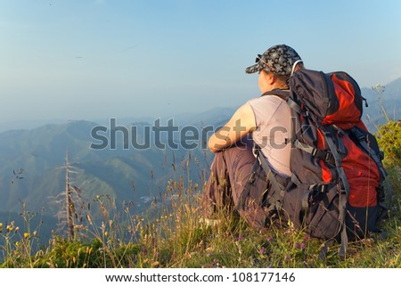 The image of a young woman sitting at the top of the mountain and looking at the high mountain peaks at sunset, Kazakhstan.