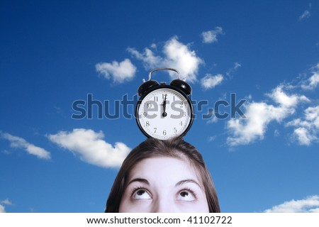The image of an alarm clock costing on a head of the girl. - stock photo