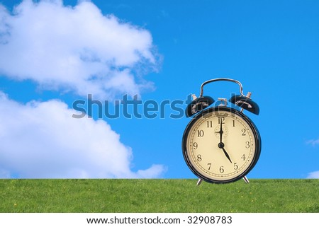 The image of an alarm clock on a green glade on a background of the sky. - stock photo