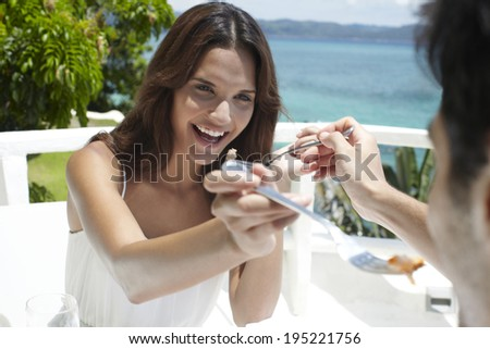 the image of couple sharing food at restaurant