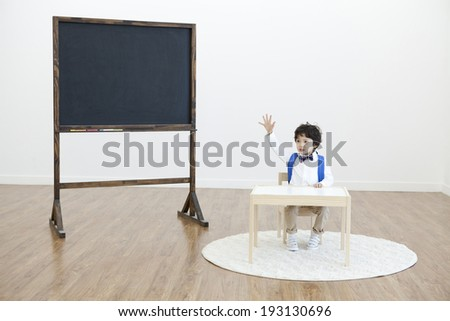 the image of cute Asian kid at school desk