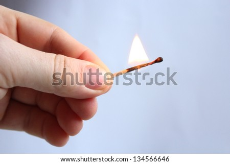 the image of hand with blazing match - stock photo