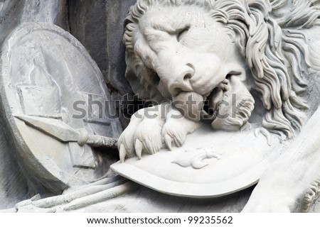 """The image of monument """"The Dying Lion"""", which made inside the cliff. The lion is the symbol of the bravery of Swiss Guards who died bravely in the Tuileries in Paris in 1792 - stock photo"""