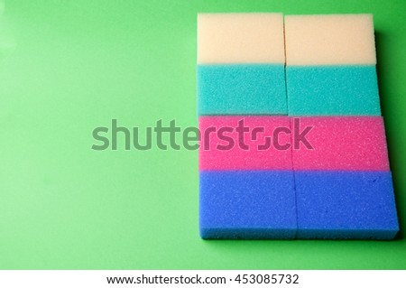The image of sponge on a green background. - stock photo