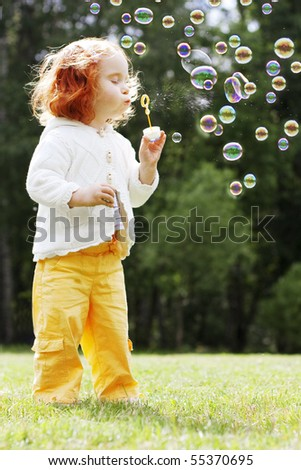 The image of the girl puts the bubbles in the park - stock photo
